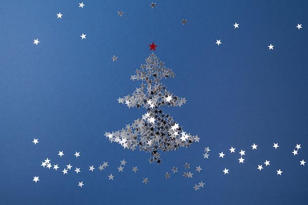Arbre de noël fait de paillettes en forme d'étoiles sur la composition de noël nouvel an bleu