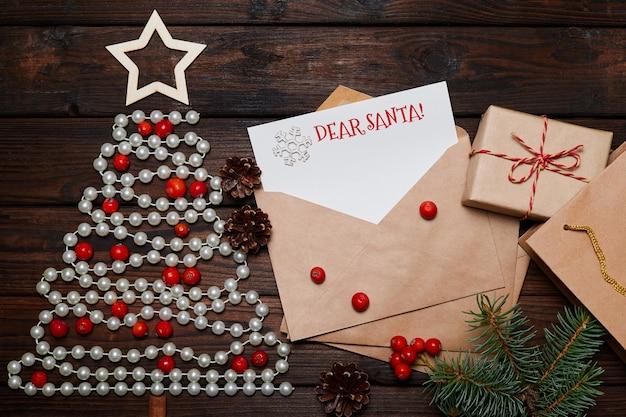 Arbre de noël fait de perles et lettre dans une enveloppe avec l'inscription joyeux noël