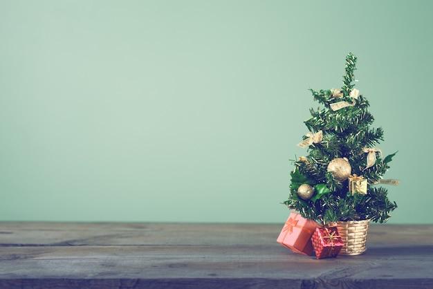 L'arbre de noël festif se dresse sur des planches sombres.