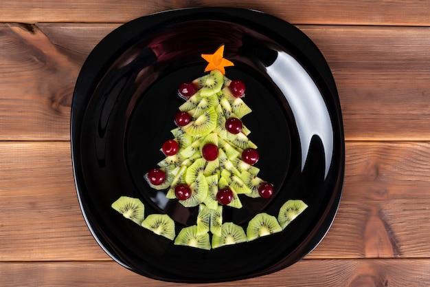 Arbre de noël de fruits et de baies de kiwi sur une plaque noire