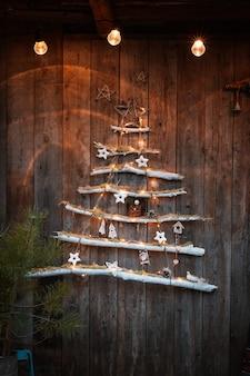 Arbre de noël à la mode moderne minimaliste sur un fond en bois rustique. décorations de noël de vos propres mains dans un style scandinave rustique.