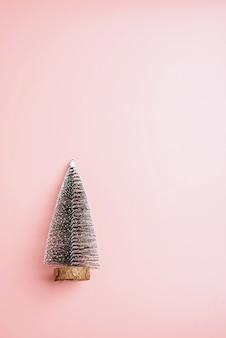 Arbre de noël neige fond rose pastel. concept de vacances minimal. nouvel an simple compo