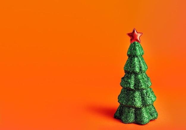 Arbre de noël nouvel an avec étoile rouge sur le dessus. fond orange avec fond de paillettes de paillettes miniatures créatives arbre de noël.
