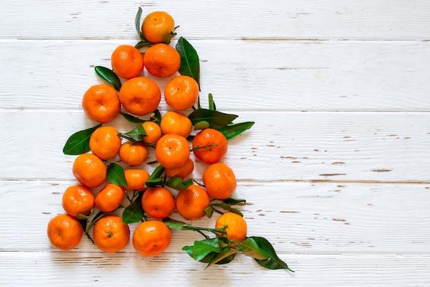 Arbre de noël nouvel an de mandarines sur fond de bois blanc. symbole du nouvel an en russie