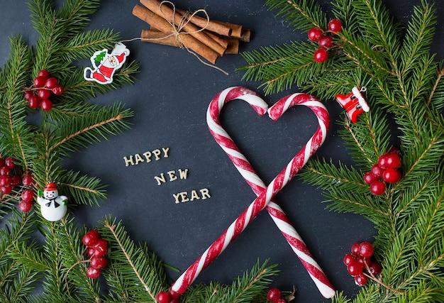 Arbre de noël avec des ornements et des bonbons sur fond noir. l'inscription bonne année.