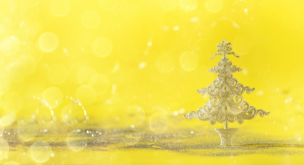 Arbre de noël de paillettes d'argent sur fond jaune avec des lumières bokeh, espace de la copie.