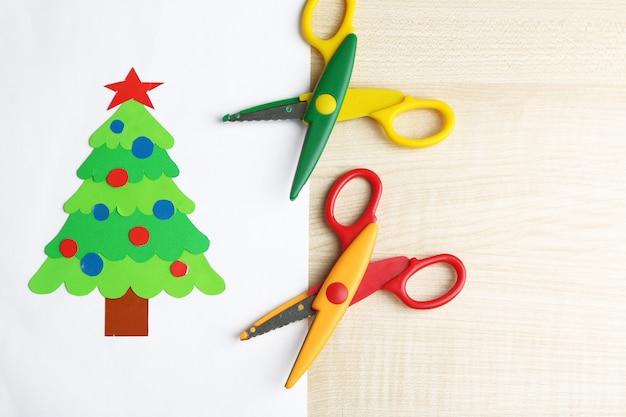 Arbre de noël en papier créatif sur feuille de papier blanc, ciseaux et crayons colorés sur fond de table de couleur
