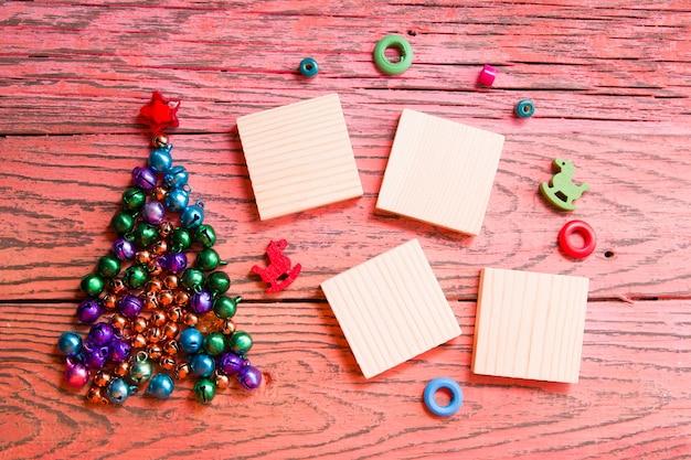Arbre en perles et cloches brillantes, carrés en bois pour la date de votre nouvel an, fond en bois rouge