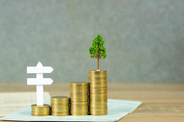 Arbre qui pousse sur des tas de pièces d'or et livre de compte ou de crédit et panneau de bois blanc