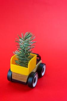 Arbres de noël à l'arrière d'une petite voiture sur fond rouge du nouvel an.