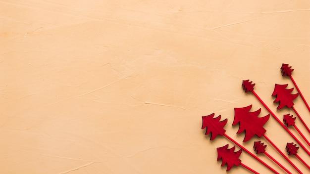 Arbres de noël en bois rouges sur une table beige