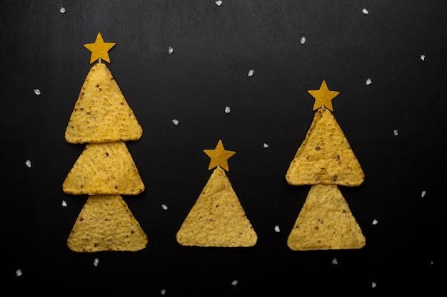 Arbres de noël fabriqués à partir de chips de nachos avec du fromage sur fond noir