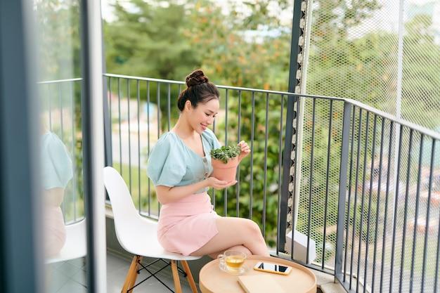 Les arbres sont dans un pot qui est placé sur le bord du balcon et une femme le cueille de là