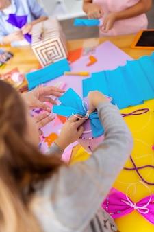Arc sur la boîte. écolière aux cheveux noirs mettant un arc en papier bleu sur une boîte présente à la leçon à l'école
