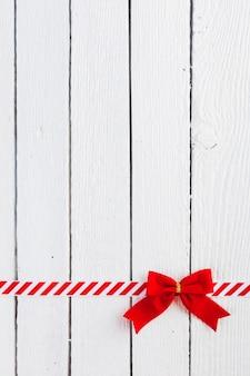 Arc cadeau rouge avec ruban sur table