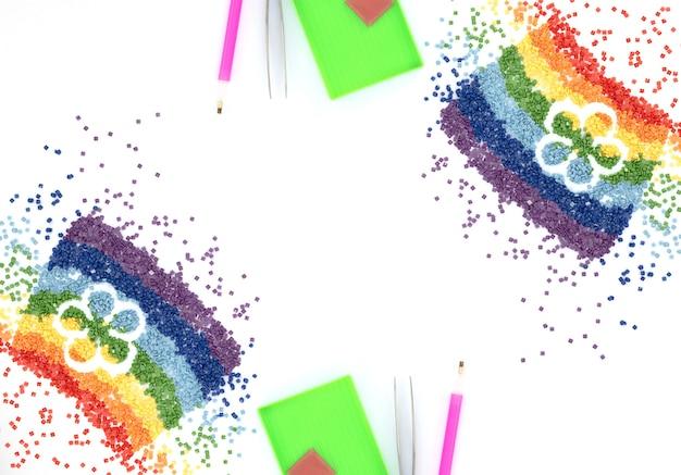 L'arc-en-ciel de cristaux colorés avec forme de fleur, pince à épiler, stylet et plateau pour broderie au diamant, mosaïque sur blanc