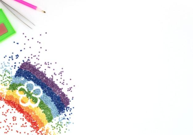 L'arc-en-ciel de cristaux colorés avec une forme de fleur, une pince à épiler, un stylet et un plateau pour la broderie au diamant