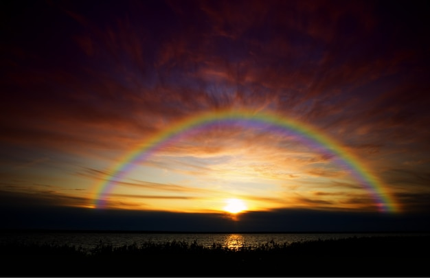 Arc-en-ciel dramatique capturé pendant le fond de paysage de coucher du soleil