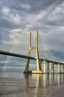 Arc-en-ciel sur le pont vasco de gama, lisbonne, portugal