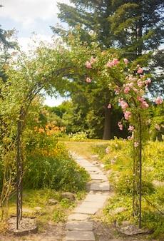Arc décoratif avec des roses dans le jardin d'été