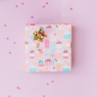 Arc doré sur une boîte cadeau emballée sur fond rose