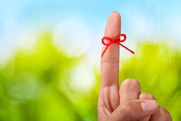 Arc de fil rouge sur un doigt humain