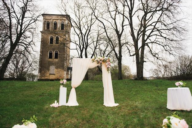 Arc de mariage décoré de tissu et de fleurs à l'extérieur. beau mariage mis en place. cérémonie de mariage sur pelouse verte dans le jardin. partie du décor festif, arrangement floral.