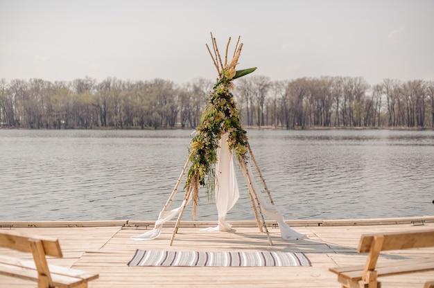 Arc de mariage élégant en poutres en bois, tissu blanc et décoré de fleurs tropicales