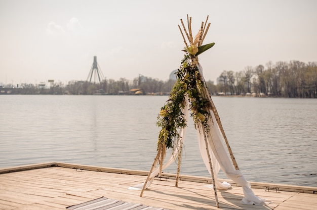 Arc de mariage fait à la main avec poutres en bois, tissu blanc et décoré de fleurs tropicales
