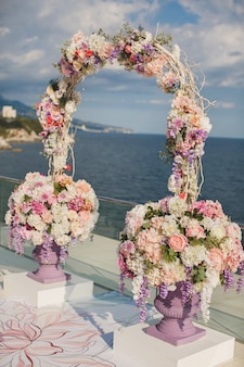 Arc de mariage avec des fleurs fraîches sur un fond de mer. vases à fleurs fraîches.