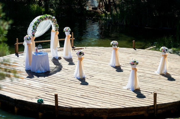 Arc de mariage joliment décoré et une petite table, des bouquets de fleurs préparés pour la cérémonie en plein air.