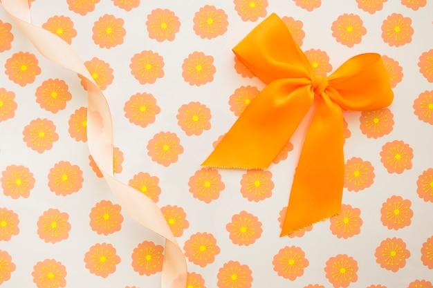 Un arc orange et un ruban frisé sur du papier cadeau floral