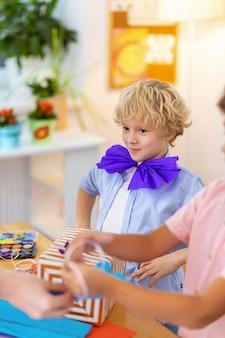 Arc en papier bleu. gai écolier aux cheveux blonds portant un arc en papier bleu à la leçon d'art