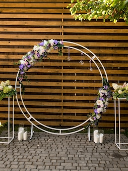 Arc rond avec des fleurs violettes fraîches. partie du décor festif, composition florale.