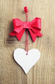 Arc rouge avec un coeur fait de papier sur un fond en bois