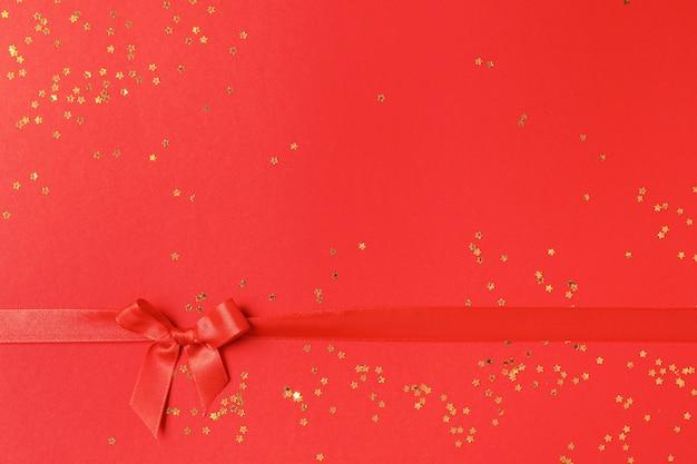 Arc rouge avec des confettis dorés sur rouge. style de noël minimal et concept de vacances.