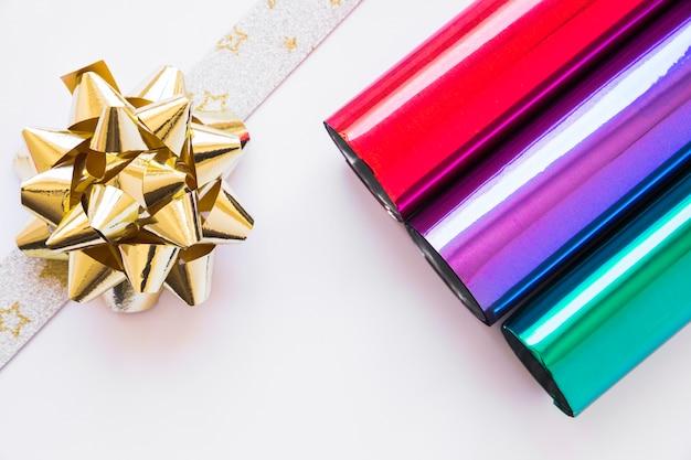 Arc de ruban doré et papier cadeau brillant enroulé sur fond blanc