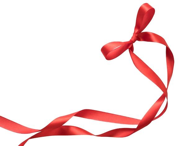 Arc de ruban rouge et boucle isolé sur fond blanc.