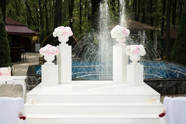 Arch à la cérémonie de mariage avec des fleurs sur le fond d'une fontaine