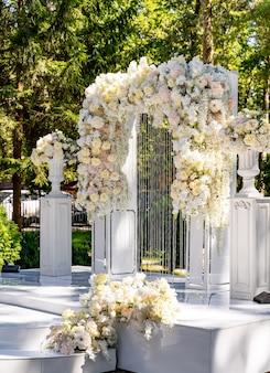 Arche de mariage dans le jardin. arc blanc décoré de fleurs tendres et claires.