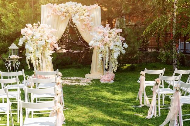 Arche de mariage décorée de tissu et de fleurs à l'extérieur