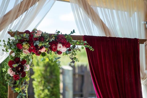 Arche de mariage. fleurs rouges et rideaux bordeaux