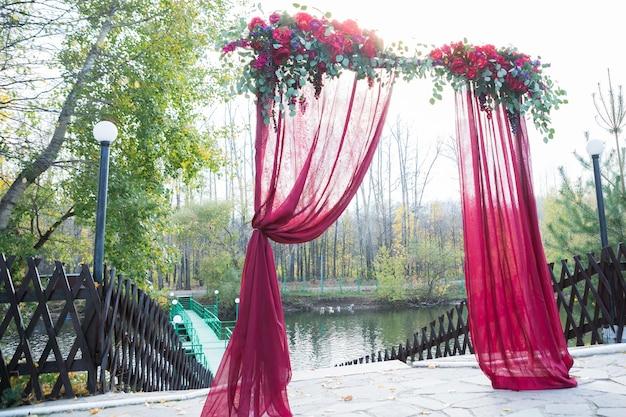 L'arche pour la cérémonie de mariage, décorée de fleurs en tissu et de verdure, se trouve dans une forêt de pins