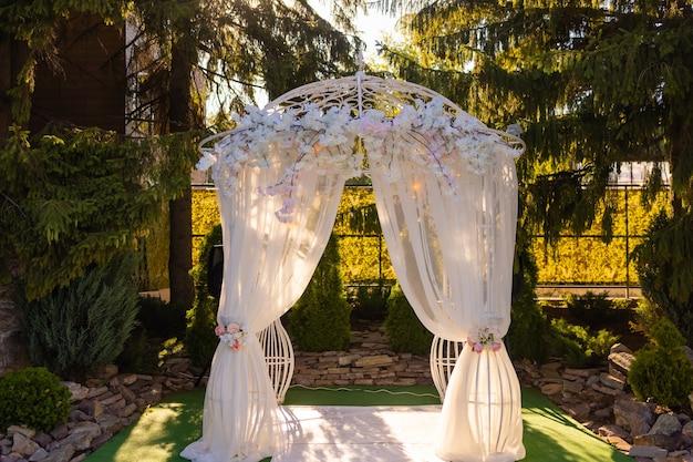 L'arche pour la cérémonie de mariage décorée de fleurs en tissu et de verdure se trouve dans une forêt de pins
