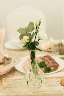 Arche sur table de fête jeunes mariés recouverte d'une nappe et décorée de composition de fleurs et de verdure, bougies dans la salle de banquet de mariage.