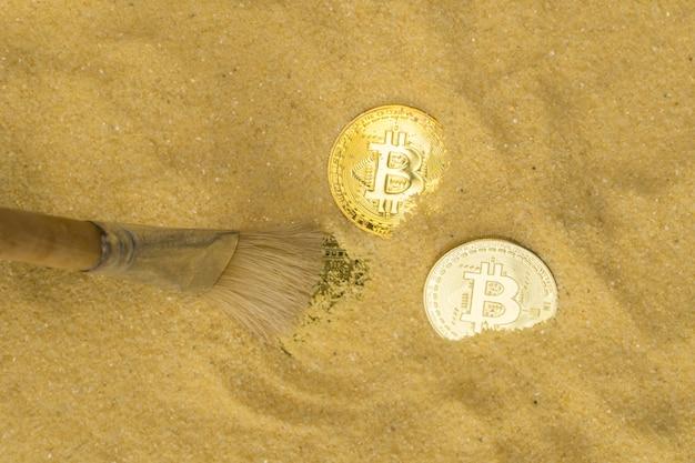 Un archéologue avec une brosse efface la pièce de bitcoin sur le sable doré crypto-monnaie minière