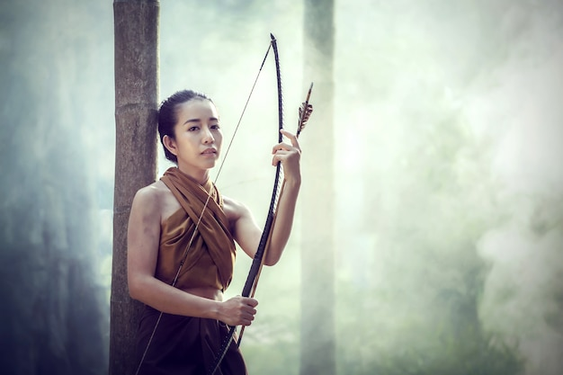 Archer de belle femme thaïlandaise avec longbow et flèches dans le style vintage de la forêt fond à la thaïlande.