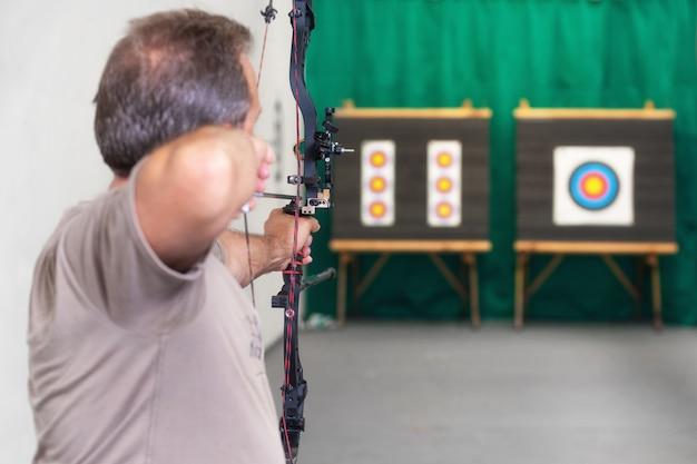 Archer senior entraînant avec l'arc. tirer sur la cible
