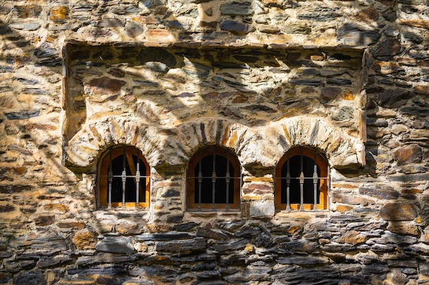 Arches de fenêtre texturées en pierre avec des ombres d'arbres