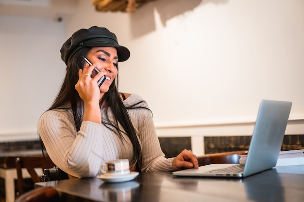 Une architecte brune latina souriante faisant un appel de travail avec un ordinateur portable dans un café